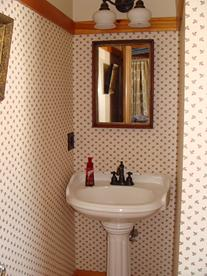 pedestal sink and mirror in the Chocolate room